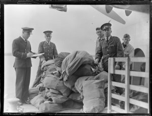 Tasman Empire Airways Ltd staff members loading mail bags onto aircraft