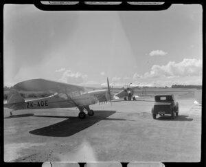 Two aircraft, Auster J1 (ZK-AQE) and de Havilland DH 82A Tiger Moth (ZK-AIF), parked on the tarmac at Aircraft Service, Mangere, Manukau City, Auckland