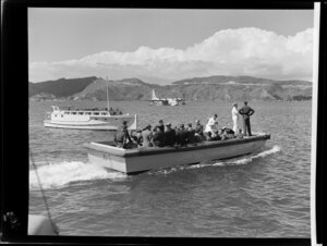 A boat ferries unidentified passengers and Tasman Empire Airways Limited crew to the Short S.45 Solent flying boat, R.M.A Ararangi (ZK-AMM), which is moored in the background, Evans Bay, Wellington