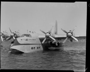 Unidentified passengers and Tasman Empire Airways Limited crew board the Short S.45 Solent flying boat, R.M.A Araragi (ZK-AMM), from a boat drawn up alongside it, Evans Bay, Wellington