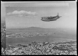 The Tasman Empire Airways Limited Short Solent flying boat RMA Ararangi (ZK-AMM) above Auckland City, including Waitemata Harbour, Devonport, and Rangitoto Island