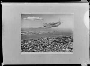 The Tasman Empire Airways Limited Short Solent flying boat RMA Ararangi (ZK-AMM) over Auckland, including Waitemata Harbour, Devonport, and Rangitoto Island