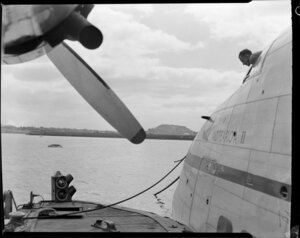 Tasman Empire Airways Ltd pilot lights on the pontoon, Mechanics Bay, Auckland with the Solent seaplane Aotearoa II moored beside it