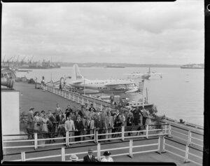 Passengers waiting to board the Tasman Empire Airways Ltd Solent seaplane Aotearoa II ZK-AML, Mechanics Bay, Auckland