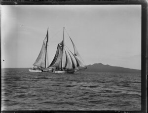 Sailing ship Ngaru carrying timber, Waitemata Harbour, Auckland Region, with Rangitoto Island in the background