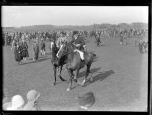 Two unidentified men on horseback amongst the crowds at the Pakuranga point to point hunt, Auckland