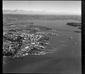 Auckland City looking towards Waitakere City, including Port, Railway Station, Harbour Bridge, and Waitemata Harbour