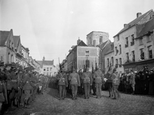 New Zealand troops marching through the bombed town of Le Quesnoy, France