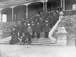 Winkelmann, Henry 1860-1931 :Captain and Mrs H Goodwyn-Archer with uniformed residents outside Ranfurly Veterans' Home in Mount Roskill, Auckland
