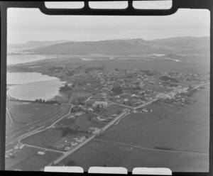 Waikouaiti, Otago District, view over town showing Palmerston-Waikouaiti Road (State Highway 1) with racecourse next to Hawksbury Lagoon wildlife refuge, surrounded by farmland, with Waikouaiti Beach and Karitane Inlet with hills beyond