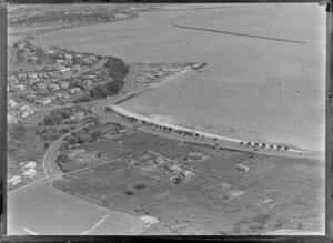 Orakei, Auckland, view of Maori settlement at Orakei Domain, Okahu Bay, with beach and Tamaki Drive with several houses and meeting house on scrubland foreground next to sports field, residential houses surround with Royal Akarana Yacht Club and Hobson Bay beyond