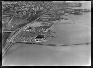Mechanics Bay, Auckland City, showing Auckland Harbour Wharf area with TEAL (Tasman Empire Airways Limited) Air Base with hanger and flying boats on land and harbour, Tamaki Drive and Quay Street, view west to ships docking, rail yards and City Centre beyond