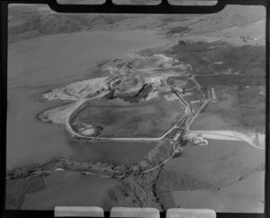 Close-up view of Huntly open cast coal mine beside lake, Waikato District, showing open pit with heavy machinery, buildings with farmland beyond