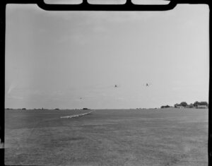 Aircraft Services aerial advertising, Mangere, South Auckland, showing two bi-planes [Tiger Moths] taking off from grass runway, towing advertising banner