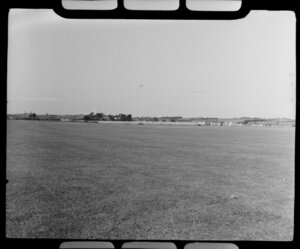 Aircraft Services aerial advertising, Mangere, South Auckland, showing one bi-planes [Tiger Moths] in the distance above grass runway, towing advertising banner