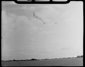 Aircraft Services aerial advertising, Mangere, South Auckland, showing two bi-planes [Tiger Moths] above grass runway, one towing advertising banner 'For Aerial Advertising Phone 19631'