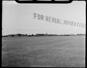 Aircraft Services aerial advertising, Mangere, South Auckland, showing banner 'For Aerial Advertising' lifting off ground, grass runway