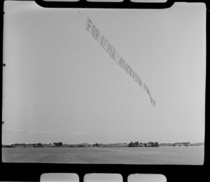 Aircraft Services aerial advertising, Mangere, South Auckland, showing banner 'For Aerial Advertising Phone 19631' just off ground, grass runway