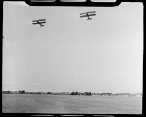 Aircraft Services aerial advertising, Mangere, South Auckland, showing two bi-planes [Tiger Moths] taking off from grass runway, with tow ropes trailing behind