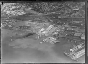 Cargo ships, stacks of timber and car ferry, wharf for exports, Auckland