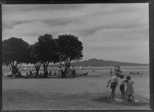 Mission Bay, Auckland, showing people on the beach watching yachting regatta and Rangitoto Island in the background