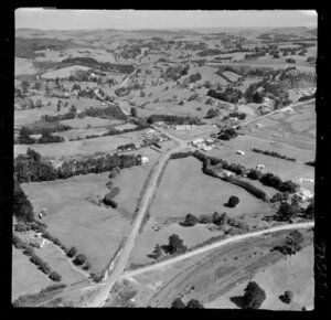 Waimauku, Auckland, showing intersection of State Highway 16 with Muriwai Road and Waimauku-Station Roads, with school, tennis courts and lawn bowls, farmland beyond