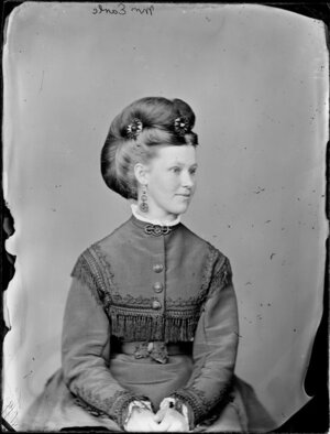 Three quarters portrait of Mrs Earle with her hair dressed in an intricate upswept style, wearing a fringed and embroidered bodice and skirt