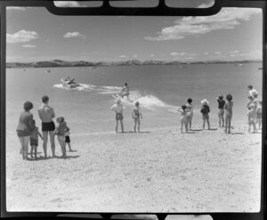 People enjoying a day at Maraetai beach, Auckland, including a water skier being towed out to sea in the background
