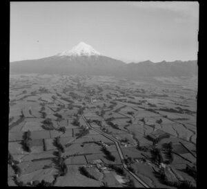 View to Mount Taranaki and the Pouakai Range over farmland with tree grove wind breaks and farm buildings, with [Carrington Road] in foreground