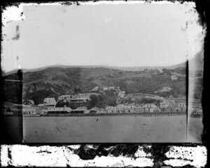 View of Wellington, from a pier near the site of the Wellington Railway Station, showing buildings along Lambton Quay including Sweeney's Nelson Hotel, a manufacturing confectioner, and houses on hill behind