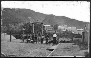 Unidentified group next to swing bridge, Hobson Street, Thorndon, Wellington, including houses on Tinakori Road in background