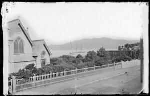 Mulgrave Street, Thorndon, Wellington, showing part of St Paul's Anglican church and a building under construction, ship in Wellington Harbour in background