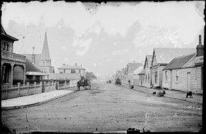 View from Pipitea Street of Mulgrave Street, Thorndon, Wellington, showing buildings on both sides of street and children sitting on footpath