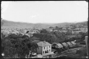 Overlooking Thorndon, towards Wellington Harbour and Oriental Bay, showing the armed constabulary cottages on corner of Grant Road and Park Street, and buildings on Tinakori Road