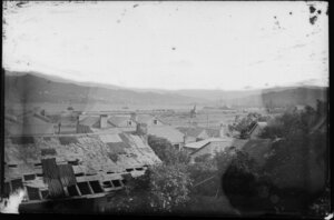 View across cottage roofs towards Wellington Harbour, showing railway yards and ships docked at wharves in distance