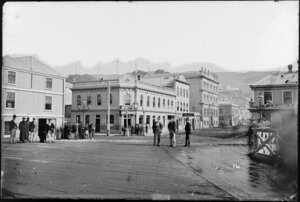 Intersection of Grey Street and Customhouse Quay, Wellington, showing groups of men standing in street, and buildings the Pier Hotel, Post Office Hotel, and the post office