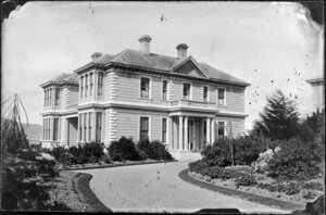 A two-storied house with a gravel driveway and landscaped garden, probably Wellington