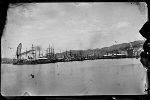 Queens Wharf, Wellington, showing ships docked at wharves and buildings on Customhouse Quay and Jervois Quay, including the Chief Post Office