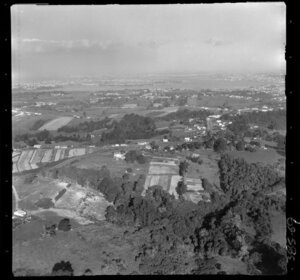 Glenfield, North Shore, Auckland, showing road over hill top with houses, fields and trees, with city and inner harbour