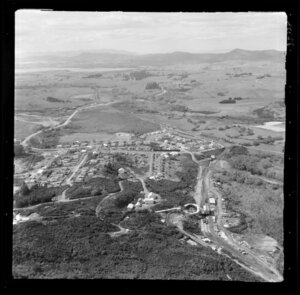 Rotowaro, Waikato District, showing a coal mining area with access roads and residential housing on hill top and coal loading area with rail lines leading down to rail yards in valley below, view to lake Waahi and Huntly beyond