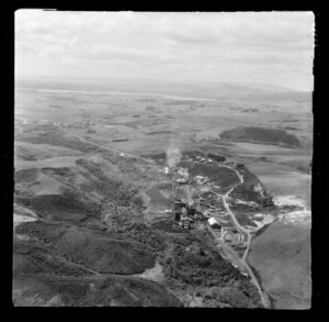 Glen Afton, Waikato, showing coal mining area, view to Pukemiro Collieries coal processing plant with railway in valley next to access roads with residential housing on ridge above, with Lake Waahi and Huntly beyond
