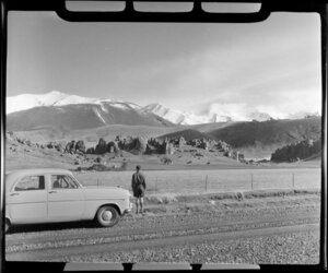 Car parked on the road in rural Canterbury, with Castle Rocks and Porters Pass in the background