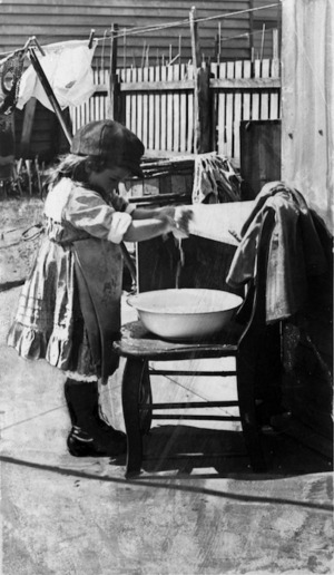 A young child washing doll's clothes in a basin
