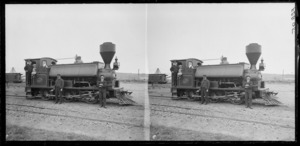 Steam locomotive at railway yards, including unidentified railways workers and a small girl seated in train cab, Dunedin area, Otago Region