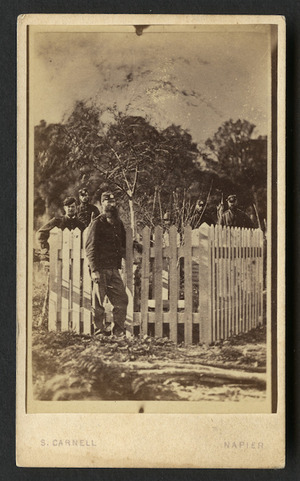 Carnell, Samuel 1832-1920 : Photograph of unidentified man dressed in uniform with other uniformed men in background