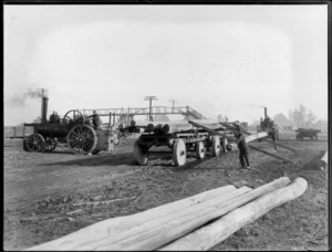Men using a steam traction engine to pull [telegraph?] poles onto a wagon, showing a steel bridge in background, Sockburn, Christchurch