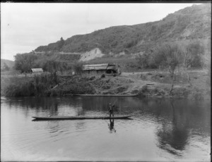 The Landing, Taumarunui, with an unidentified Maori man in a waka on the [Wanganui?] River, and a dwelling, with wooden walls and roof on the bank behind