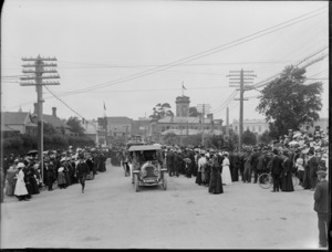 Crowds gather to watch motor cars in the parade, on an unidentified street, Timaru, with the clock tower in the background, to celebrate the coronation of George V