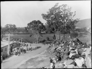 Crowds gather to watch a cycling race, Christchurch, with two cyclists at the bottom of the hill