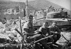 Members of the 4 NZ Armoured Brigade alongside a Sherman tank, after the capture of Cassino, Italy - Photograph taken by George Kaye